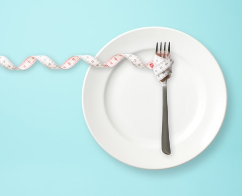 Teller mit Gabel und Maßband Symbolbild Ernährung